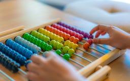 Mão que conta o ábaco colorido dos grânulos fotografia de stock