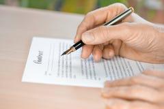 Mão que corrige um contrato com pena de fonte Imagem de Stock Royalty Free