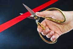 Mão que corta a fita vermelha com tesouras. Fotografia de Stock