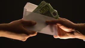 Mão que dá euro no envelope isolado no preto, na corrupção ou no salário ilegal vídeos de arquivo