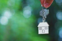 Mão que dá a tecla HOME com o keyring da casa do amor com o jardim verde do borrão, fundo, conceito doce da casa fotos de stock