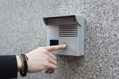 Mão que empurra o botão da campainha elétrica em uma parede foto de stock