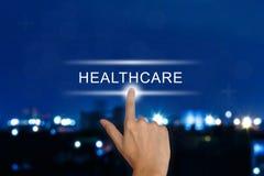 Mão que empurra o botão dos cuidados médicos no tela táctil Foto de Stock