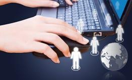 Mão que empurra o teclado do portátil com rede social. Foto de Stock