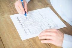 Mão que enche a aplicação do subsídio de desemprego fotografia de stock royalty free