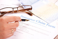 Mão que enche-se no formulário de reivindicação do seguro imagens de stock royalty free