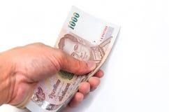 Mão que envia um volume do baht 1000 Imagem de Stock