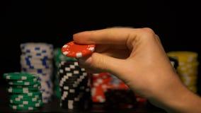 Mão que escolhe a microplaqueta vermelha entre pilhas de símbolos, probabilidades do jogo do casino, aposta afortunada vídeos de arquivo