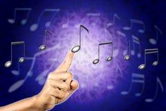 Mão que escolhe uma nota da música. Fotos de Stock Royalty Free