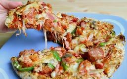 Mão que escolhe uma parte de pizza de queijo Mouthwatering da placa servida na tabela de madeira fotografia de stock