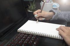 Mão que escreve para fazer a lista no caderno vazio Foto de Stock