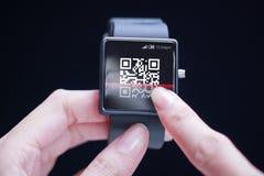 Mão que faz a varredura do código de QR no smartwatch Foto de Stock Royalty Free