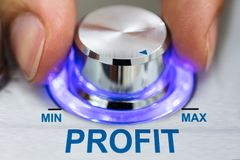Mão que gira o botão metálico pelo texto do lucro fotos de stock royalty free