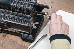 Mão que gira o punho da máquina de adição imagens de stock
