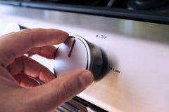 Mão que gira um botão do forno do fogão Fotografia de Stock Royalty Free
