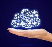 Mão que guarda ícones do computador na forma da nuvem no fundo azul Fotografia de Stock Royalty Free