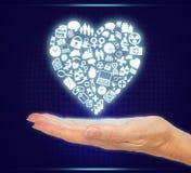 Mão que guarda ícones na forma médica do coração da saúde Fotos de Stock Royalty Free