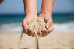 Mão que guarda a areia fotos de stock royalty free