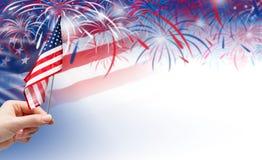 Mão que guarda a bandeira dos EUA no fundo dos fogos-de-artifício Fotografia de Stock