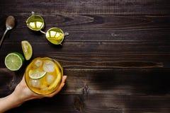 Mão que guarda a bebida do gelo Chá de gelo, limão, cal e óculos de sol na tabela de madeira, vista superior Com espaço da cópia Foto de Stock