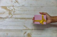 Mão que guarda a caixa de presente do Natal Presente de Natal na caixa no whi Imagem de Stock