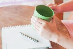 Mão que guarda a caneca verde na cafetaria Fotografia de Stock
