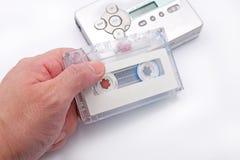 Mão que guarda a cassete de banda magnética com fundo do leitor de cassetes Fotos de Stock Royalty Free