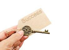 Mão que guarda a chave do vintage do metal com etiqueta do sucesso Imagem de Stock Royalty Free
