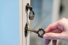 Mão que guarda a chave do vintage do metal para destravar foto de stock