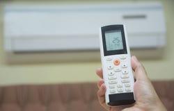 Mão que guarda de controle remoto para o condicionador de ar aberto foto de stock