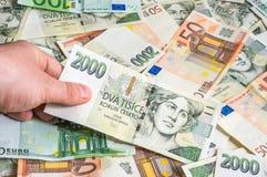 Mão que guarda dois mil coroas checas Fotografia de Stock Royalty Free