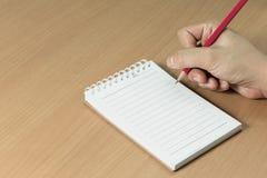 Mão que guarda a escrita vermelha do lápis no caderno Foto de Stock