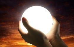 Mão que guarda a esfera clara fotos de stock