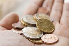 Mão que guarda euro- moedas Foto de Stock Royalty Free