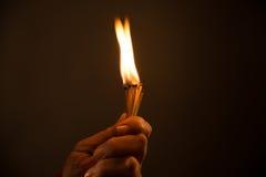 Mão que guarda fósforos ardentes tiro do estúdio, fim acima, Imagens de Stock Royalty Free
