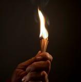 Mão que guarda fósforos ardentes tiro do estúdio, fim acima, Fotografia de Stock
