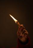 Mão que guarda fósforos ardentes tiro do estúdio, fim acima, Imagens de Stock