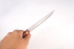Mão que guarda a faca de aço no fundo branco Foto de Stock