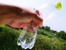 Mão que guarda a garrafa de água plástica no fundo verde borrado do jardim foto de stock