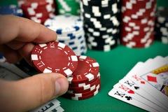Mão que guarda microplaquetas de pôquer Imagens de Stock