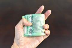 Mão que guarda a moeda dos dólares canadenses fotos de stock royalty free