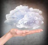 Mão que guarda a nuvem com ícones digitais diferentes Fotos de Stock