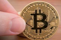 Mão que guarda o bitcoin dourado real Imagens de Stock