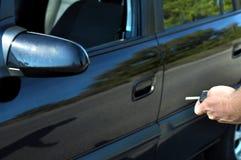 Mão que guarda o botão no carro remoto No foco seletivo dos homens a mão pressiona nos sistemas de alarme de controle remoto do c Foto de Stock Royalty Free