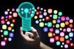 Mão que guarda o bulbo que emite-se ícones da aplicação Foto de Stock