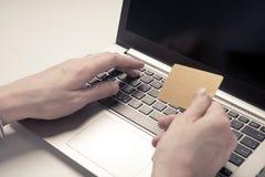 Mão que guarda o cartão de crédito e o portátil do uso Fotos de Stock Royalty Free