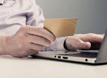 Mão que guarda o cartão de crédito e o portátil do uso Imagens de Stock Royalty Free