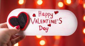 Mão que guarda o cartão feliz do dia de Valentim foto de stock