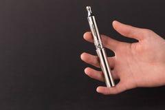Mão que guarda o cigarro eletrônico Fotografia de Stock
