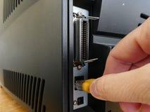 Mão que guarda o connecior dos ethernet a conectar uma impressora à rede imagens de stock